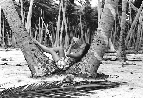 Gail drinking coconut between two palm trees, Raroia, Tuamotus, French Polynesia